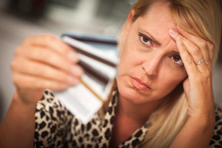 Robed vrouw schitteren op haar vele creditcards van streek.  Stockfoto