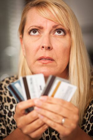 Upset Robed Woman Glaring At Her Many Credit Cards. Stock Photo - 7968452