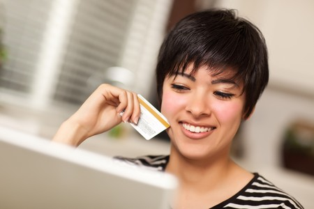 credit card: Smiling Multiethnic Woman Holding Credit Card While Using Laptop.