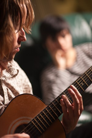 Young Musician Plays His Acoustic Guitar as Friend in the Background Listens. Stock Photo - 7968471