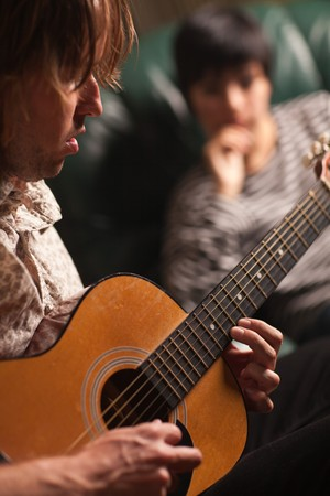 Young Musician Plays His Acoustic Guitar as Friend in the Background Listens. Stock Photo - 7968472