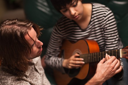 teaches: Young Male Musician Teaches Female Student How To Play the Guitar.
