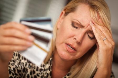 Bardzo zatroskany kobieta jej wielu kart kredytowych. Zdjęcie Seryjne