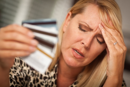 Very Upset Woman Holding Her Many Credit Cards. photo