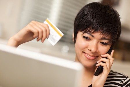 Pretty Young Multiethnic Woman Holding Phone and Credit Card Using Laptop. photo