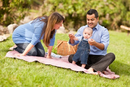 Happy Mixed Race Family Having a Picnic and Playing In The Park. photo