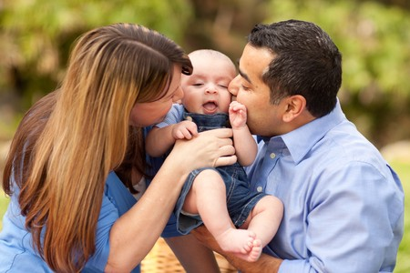 Happy Mixed Race Parents Playing with Their Giggling Son. Stock Photo - 8085203