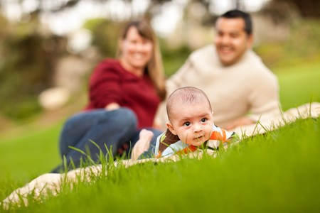 Happy Crawling Baby Boy and Mixed Race Parents Playing in the Park. photo