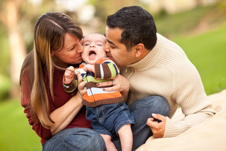 Happy Mixed Race Parents Playing with Their Giggling Son. photo
