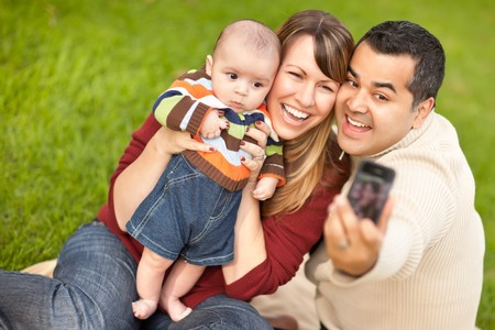 Happy Mixed Race Parents and Baby Boy Taking Self Portraits at the Park. photo