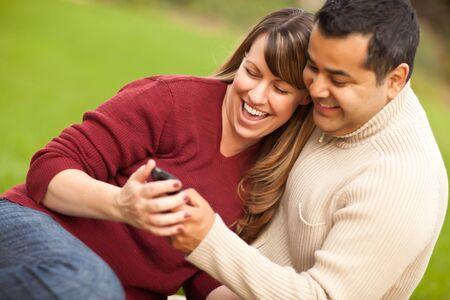 mixed race couple: Atractiva mezcla de carrera pareja disfrutando de su tel�fono de c�mara en el parque.  Foto de archivo