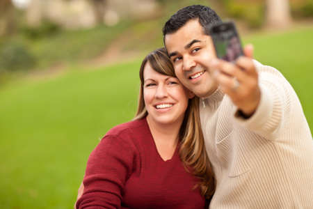 Attractive Mixed Race Couple Taking Self Portraits in the Park. photo