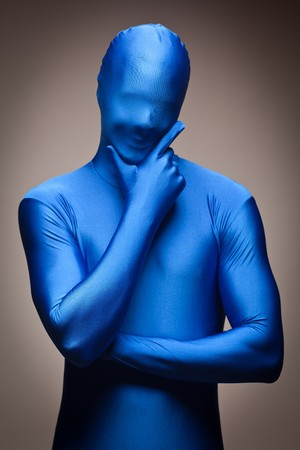 Thinking Man with Hand on Chin Wearing Full Blue Nylon Bodysuit on a Grey Background.