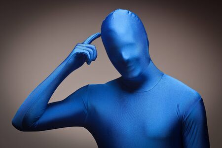 Man Wearing Full Blue Nylon Bodysuit Scratching His Head on a Grey Background.  photo