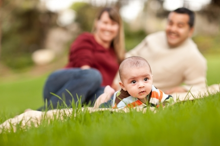 Happy Crawling Baby Boy and Mixed Race Parents Playing in the Park. Stock Photo - 8176834