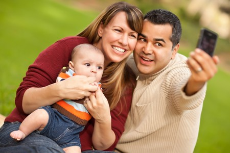 latino family: Happy Mixed Race Parents and Baby Boy Taking Self Portraits at the Park.