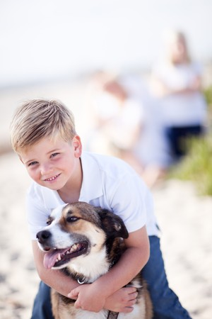 Handsome Young Boy Playing with His Dog at the Beach.  photo