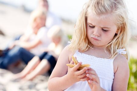 Adorable Little Blonde Girl with Starfish at The Beach.  photo