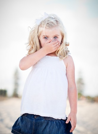 covering: Adorable Blue Eyed Girl Covering Her Mouth Outside.