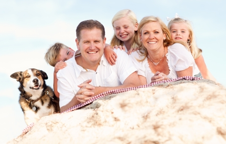 family baby: Happy Caucasian Family and Dog Portrait at the Beach One Sunny Afternoon. Stock Photo