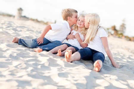 sister: Adorable Sibling Children Kissing the Youngest Girl at the Beach.