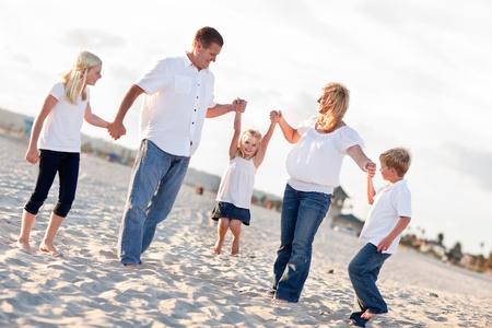 사랑스러운 작은 소녀 그녀의 부모와 가족 해변에서 함께 스윙.