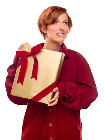Pretty Red Haired Girl Biting Her Lip Holding Wrapped Gift Isolated on a White Background. Stock Photo - 8318686