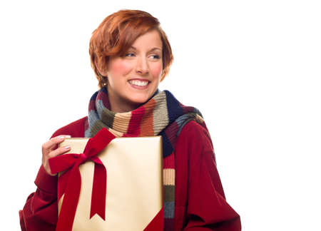 Pretty Red Haired Girl with Scarf Holding Wrapped Gift Looking Off to the Side Isolated on a White Background. Stock Photo - 8318684