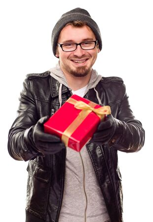 warmly: Warmly Dressed Handsome Young Man Handing Wrapped Gift Out Isolated on a White Background. Stock Photo