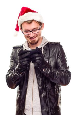Smiling Young Man with Santa Hat Using Cell Phone Isolated on a White Background. Stock Photo - 8318703