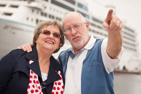 disembarking: Senior Couple On Shore in Front of Cruise Ship While on Vacation.