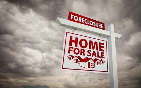 stoppage: White and Red Foreclosure Home For Sale Real Estate Sign Over Ominous Cloudy Sky.