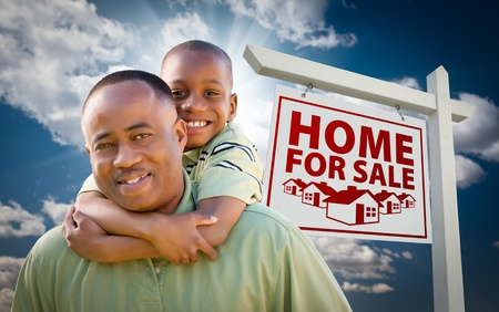 Happy African American Father with Son In Front of Home For Sale Real Estate Sign and Sky. photo