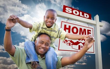 Happy African American Father with Son In Front of Sold Home For Sale Real Estate Sign and Sky. Imagens
