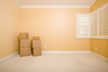 Moving Boxes in Empty Room with Copy Space on Blank Wall. photo