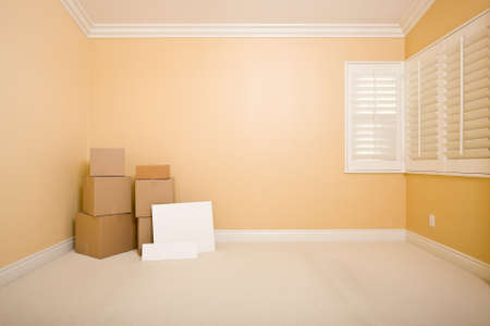 Moving Boxes and Blank Signs on Floor in Empty Room with Copy Space on Blank Wall. photo