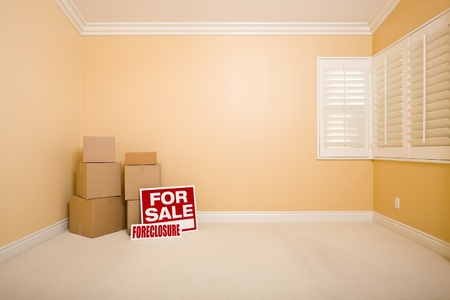 Moving Boxes, For Sale and Foreclosure Real Estate Signs on Floor in Empty Room with Copy Space on Blank Wall. photo