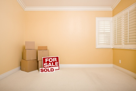 Moving Boxes, For Sale and Sold Real Estate Signs on Floor in Empty Room with Copy Space on Blank Wall. photo