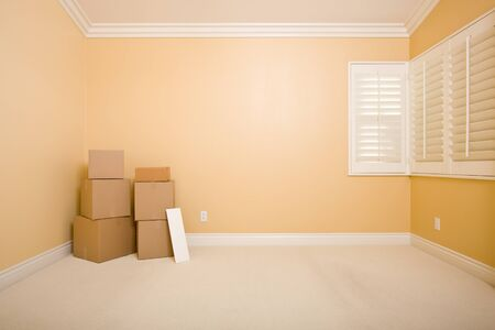 Moving Boxes and Blank Sign on Floor in Empty Room with Copy Space on Blank Wall. photo