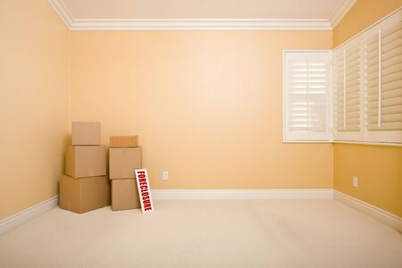 bank owned: Moving Boxes and Foreclosure Real Estate Sign on Floor in Empty Room with Copy Space on Blank Wall. Stock Photo