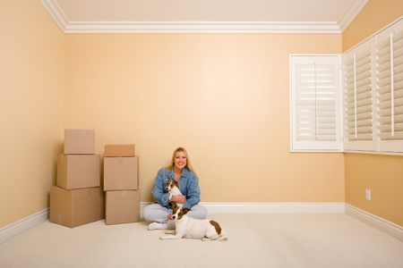 Pretty Woman and Dogs Sitting on the Floor with Moving Boxes in Empty Room photo