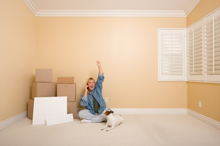Pretty Woman on the Floor Using Phone Celebrating with Moving Boxes, Blank Signs and Dog in Empty Room. photo