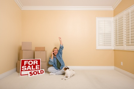 Pretty Woman Sitting on Floor Using Phone Celebrating Next to Moving Boxes, Sold Real Estate Signs and Dog in Empty Room. photo