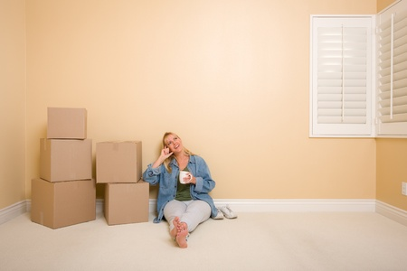 sweats: Pretty Woman Sitting on Floor with Cup Next to Moving Boxes in Empty Room. Stock Photo