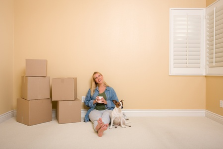 Pretty Woman Sitting on Floor with Cup Next to Moving Boxes and Dog in Empty Room. photo