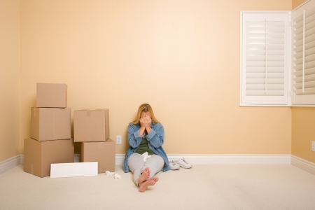 Upset Woman with Tissues on Floor Next to Boxes and Blank Sign in Empty Room. photo