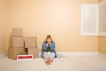 Upset Woman with Tissues on Floor Next to Boxes and Foreclosure Real Estate Sign in Empty Room. photo
