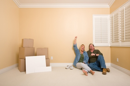 Excited Couple Relaxing on Floor Near Boxes and Blank Real Estate Signs in Empty Room photo