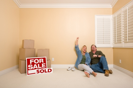 Excited Couple Relaxing on Floor Near Boxes and Sold Real Estate Signs in Empty Room. photo