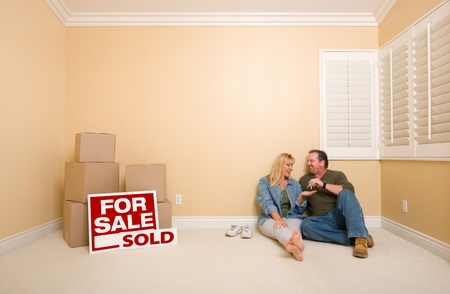 Excited Couple With New Keys Relaxing on Floor Near Boxes and Sold Real Estate Signs in Empty Room. photo